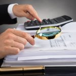 45058557 - close-up of businessperson hands checking invoice with magnifying glass at desk